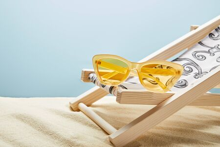 Yellow sunglasses and deck chair on sand on blue background