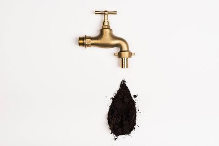 Top view of faucet and black soil on white background 写真素材