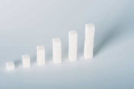 White sugar cubes arranged in stacks on grey background with copy space Imagens