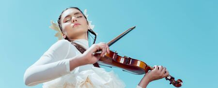 Low angle view of tender woman in white swan costume standing on blue sky background with violin Imagens