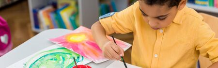 Panoramic shot of African American kid painting while holding paintbrush