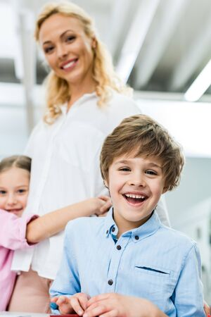 Selective focus of cheerful kid smiling while looking at camera near woman