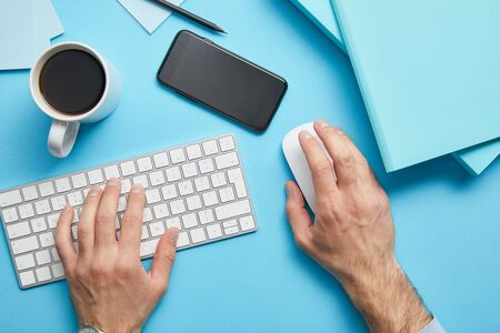 Cropped view of man using computer keyboard and computer mouse at workplace with papers, smartphone and cup of coffee on blue background