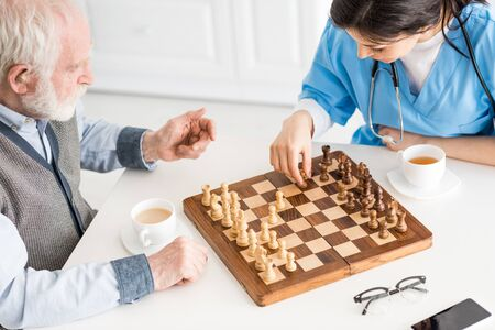 High angle view of nurse with senior man sitting on kitchen, playing in chess Foto de archivo - 125525677