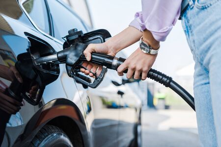 Cropped view of woman holding fuel pump while refueling car with benzine Stock Photo