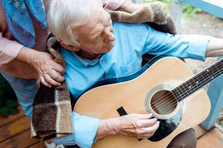 Cropped view of senior woman near husband playing acoustic guitar