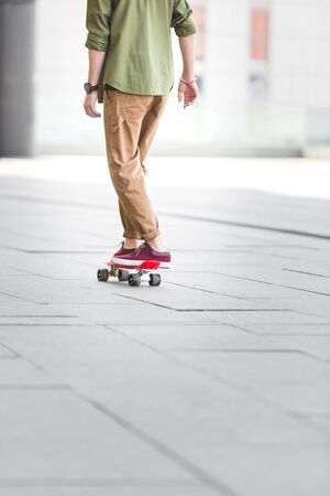 Cropped view of man riding on penny board