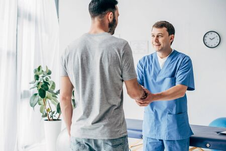 Back view of patient shaking hands with doctor in massage cabinet at clinic Reklamní fotografie