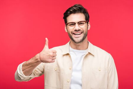 Handsome smiling man showing thumb up isolated on pink background