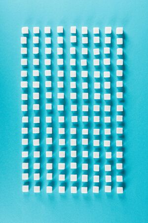 Top view of white sugar cubes arranged in rows on blue surface background