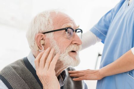 Profile of happy bearded man with hearing aid, looking away Stock Photo