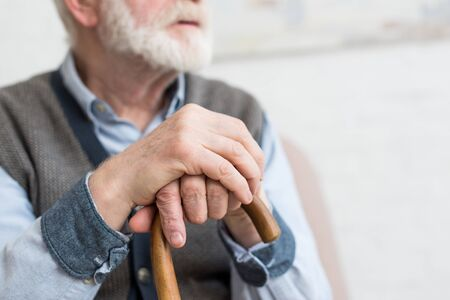Cropped view of elderly man with walking stick in hands Stockfoto