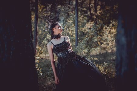 Selective focus of beautiful woman in black witch costume standing between trees