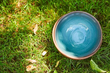 Top view of blue ceramic bowl on green grass