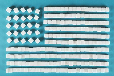 Symbol of USA national flag made of white sugar cubes on blue surface Stockfoto