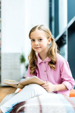 Selective focus of cute and cheerful kid sitting and holding book in library