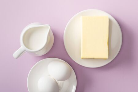 Top view of butter, milk jug and boiled eggs on white plates on violet background Stock Photo