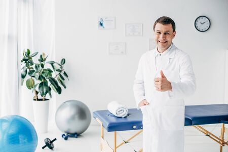 Good-looking smiling chiropractor showing thumb up in hospital