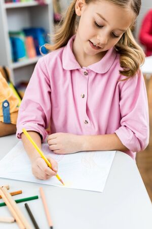 Selective focus of cute kid drawing with yellow pencil on paper 版權商用圖片