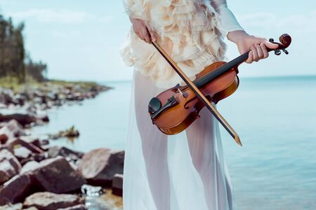 Cropped view of elegant woman in white swan costume with violin standing on river background Standard-Bild - 125526247