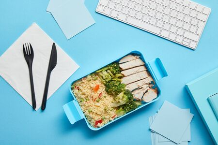 Top view of lunch box with delicious rice with chicken and broccoli at workplace with computer keyboard on blue background