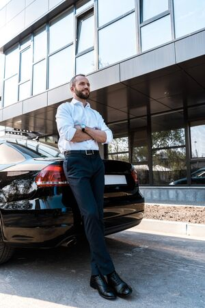 Low angle view of handsome man standing with crossed arms near black car
