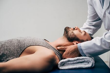 Chiropractor massaging neck of handsome man lying on Massage Table on grey background