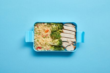 Top view of lunch box with tasty chicken, risotto and broccoli on blue background