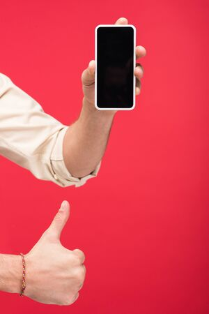 Cropped view of man holding smartphone with blank screen and doing thumb up sign isolated on pink background Stock fotó