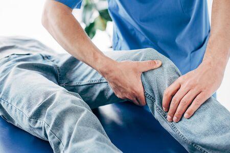 Vista recortada del quiropráctico masajeando la pierna del paciente en el hospital