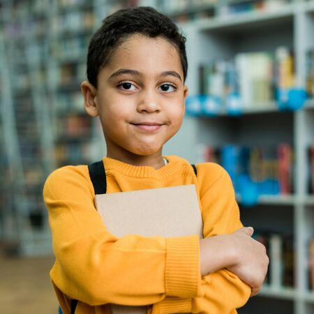 Cute African American boy smiling while holding book