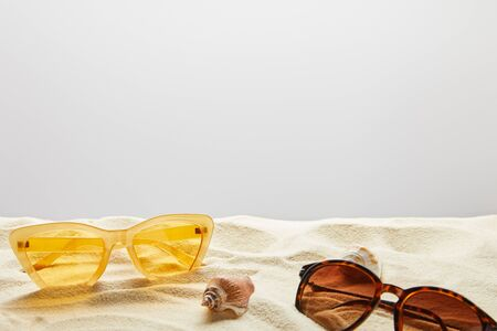 Yellow and brown stylish sunglasses on sand with seashells on grey background