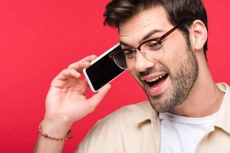 Excited man talking on smartphone isolated on pink background