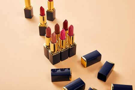 Various shades of lipsticks on beige background 写真素材