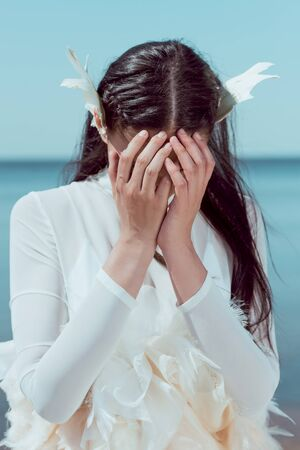 Upset woman in white swan costume standing on blue river and sky background, covering face by hands