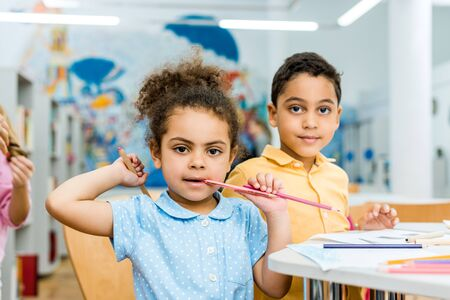 Selective focus of cute African American kid biting pencil near adorable child Stock Photo
