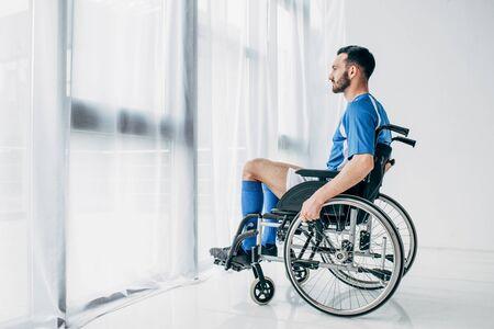 Uomo in uniforme da calcio seduto su una sedia a rotelle e guardando attraverso la finestra