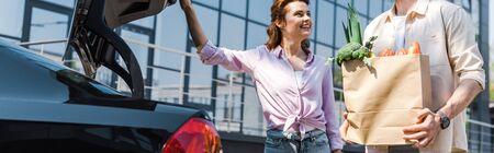Panoramic shot of happy woman looking at man holding paper bag near car Banco de Imagens