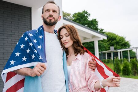 Attractive woman with closed eyes holding American flag and standing with handsome man Stock Photo