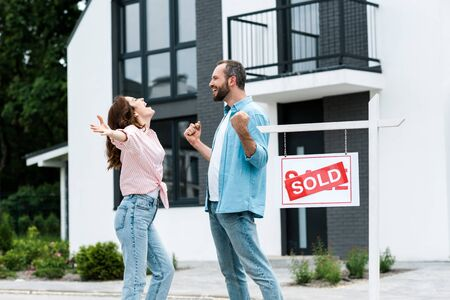 Happy man and woman celebrating near house and board with sold letters Banco de Imagens