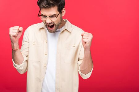 Excited handsome man with clenched fists isolated on pink background