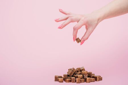 Cropped view woman with handful of white sugar cubes on isolated on pink background