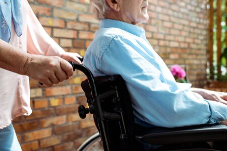 Cropped view of senior disabled man sitting in wheelchair near wife Banque d'images - 125526968