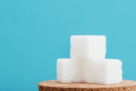 White sugar cubes on cork surface isolated on blue background with copy space