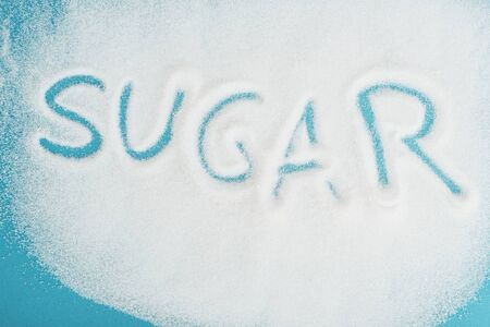 Top view of word sugar made on sprinkled white sugar crystals on blue surface