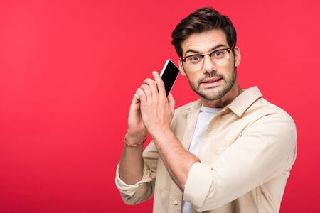 Confused man talking on smartphone and looking at camera isolated on pink background