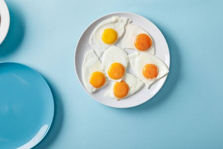 Top view of fried eggs on white plate on blue background