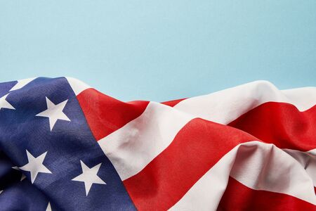Close up view of American crumpled national flag on blue background with copy space