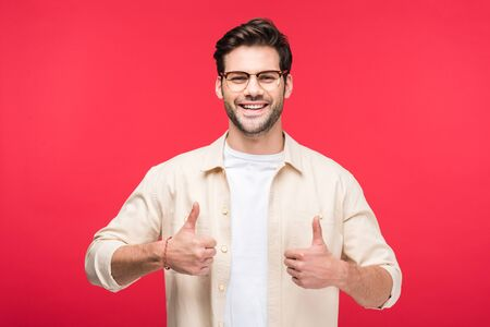 Happy handsome man showing thumbs up isolated on pink background