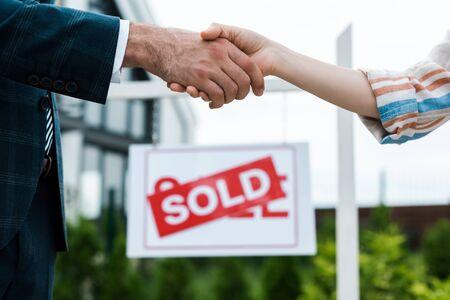 Selektiver Fokus von Makler und Frau, die sich mit verkauften Briefen die Hände in der Nähe des Boards schütteln Standard-Bild